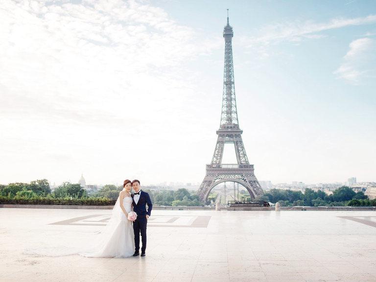 Couple posing in font of Eifel tower in Paris