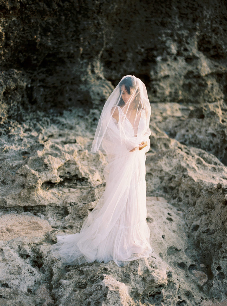 Bride with veil on the cliff on beach wedding
