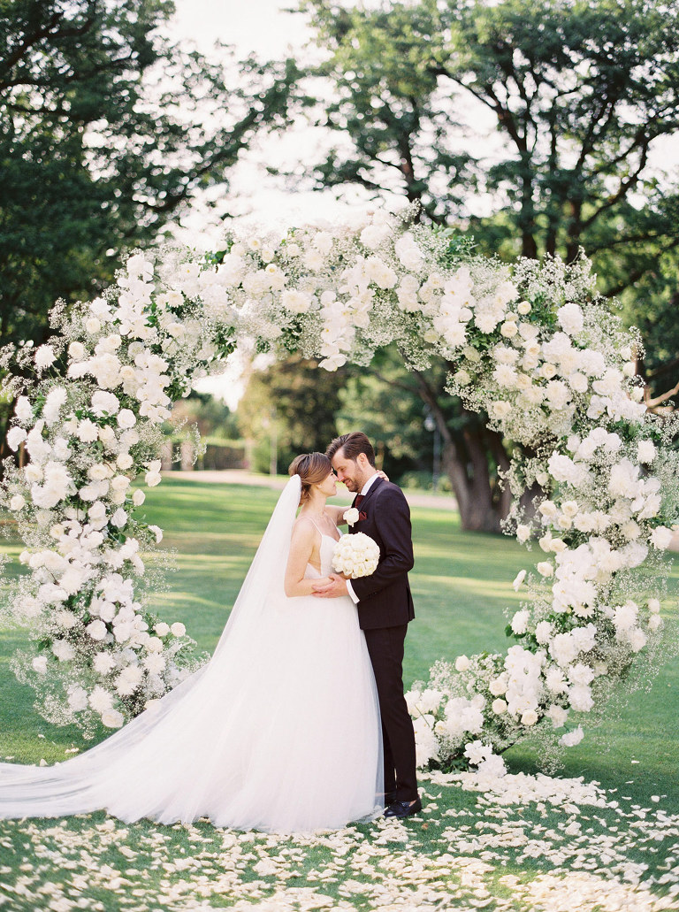 Luxury wedding day in Chateau Mcely with all white flowers wedding gate circle